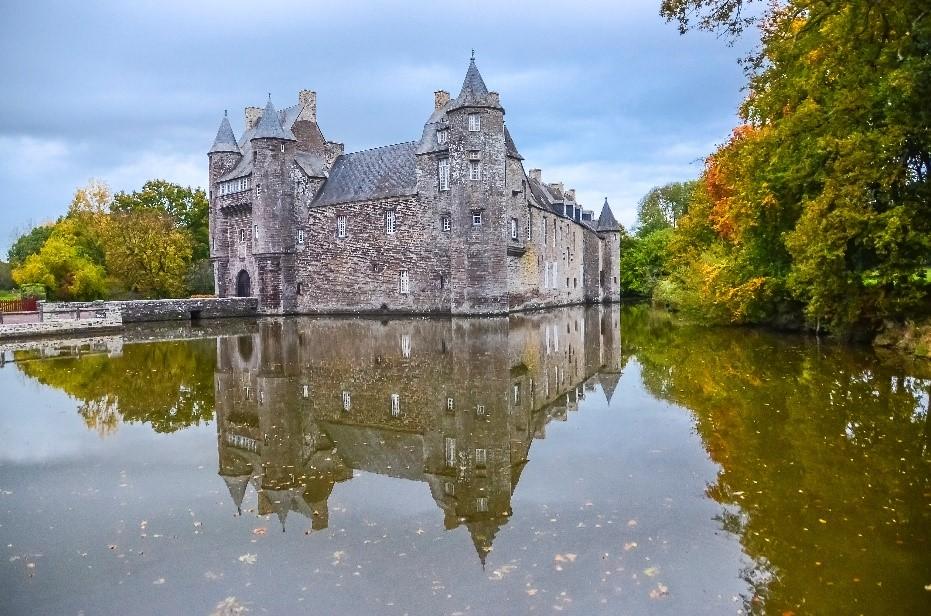 Le château de Trécesson se reflétant sur le lac.